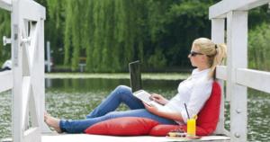 DAS SCHMÖCKWITZ: Junge Frau sitzt mit Laptop auf dem Steg am See