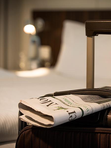 Hotelzimmer: Koffer mit Zeitung
